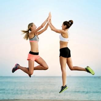 women jumping happy fitness beach sun Holmes Place