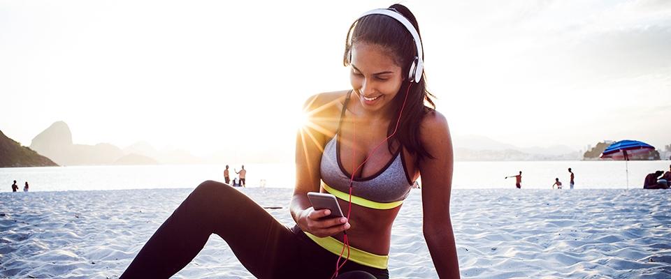 Kobieta słuchająca muzyki w słuchawkach na plaży o zachodzie słońca | Holmes Place