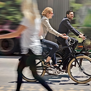 Holmes Place | Man and Woman riding bike in the street