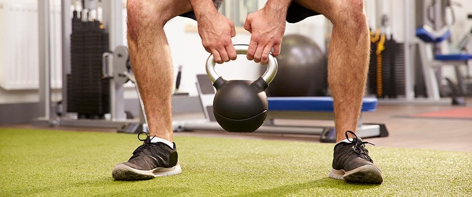 Homem a fazer exercício com kettlebell para perder peso | Holmes Place