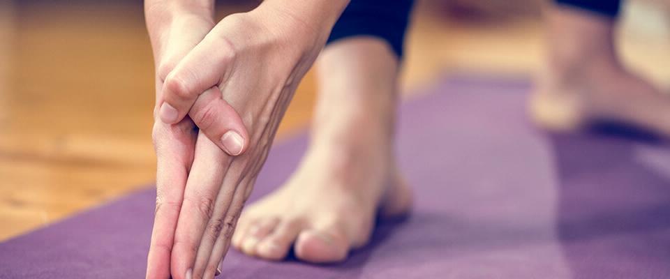 close-up mãos pés tapete yoga | Holmes Place