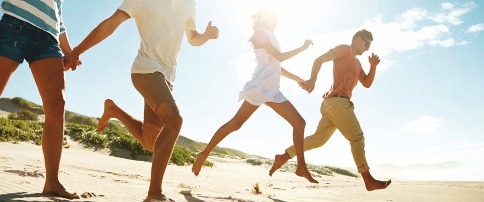 grupa osób biegnąca po plaży | Holmes Place