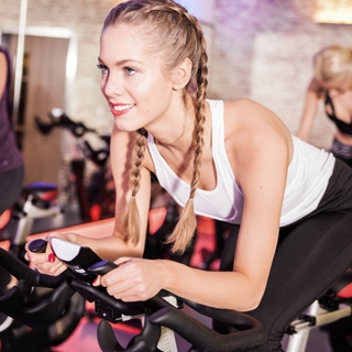 indoor cycling gym fitness women smile | Holmes Place