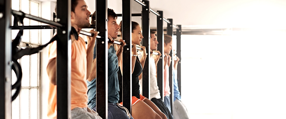 guys doing bar pull-ups in a gym