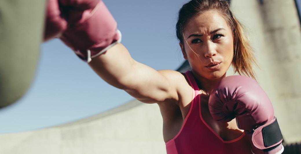 Dziewczyna w różowych rękawicach bokserskich podczas treningu PT boxing w Holmes Place