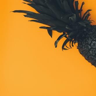 Schwarze Ananas mit organgenem Hintergrund