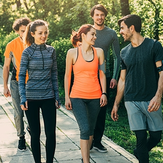happy people walking sunny outdoors park men women fitness outfits Holmes Place