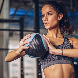 woman indoor gym training medicine ball workout fitness Holmes Place