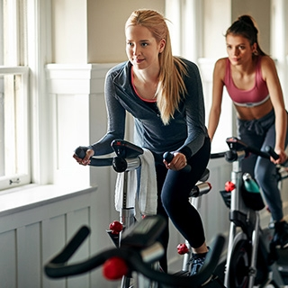 women indoor cycling bike training gym workout fitness | Holmes Place