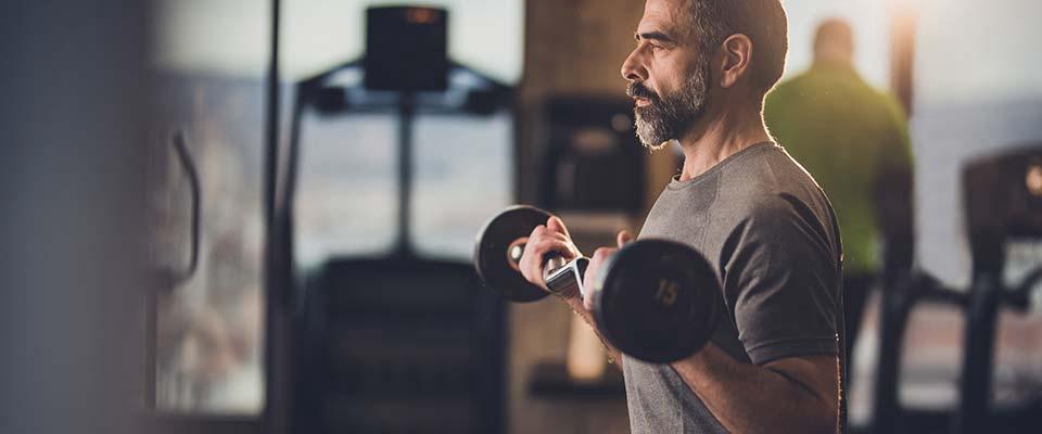 Homem a fazer bíceps | Fitness | Holmes Place