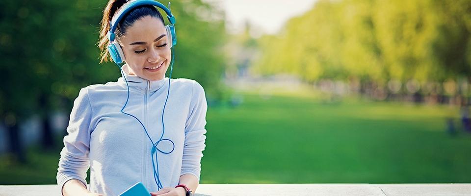 uśmiechnięta dziewczyna w słuchawkach słucha muzyki po treningu w Holmes Place