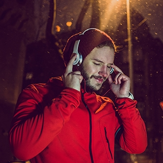 man smiling night running outdoor music headset playlist winter holmes place