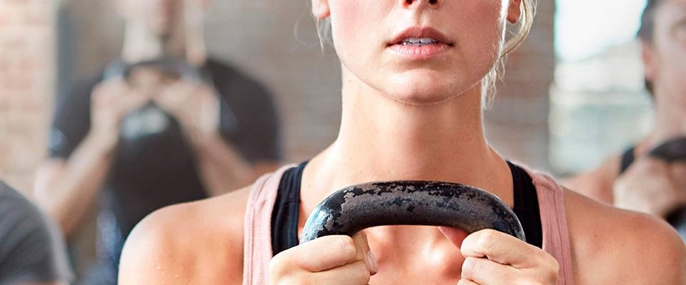 Mujer entrenando con una kettlebell | Holmes Place