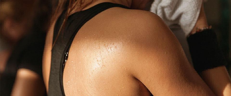 Holmes Place | woman shoulder blade close up black tank-top