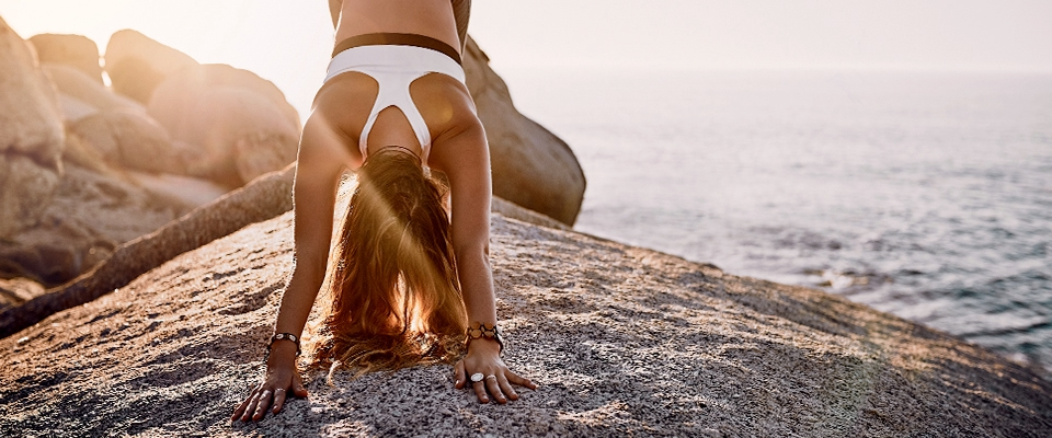 woman beach ocean yoga downward dog pose sunset | Holmes Place