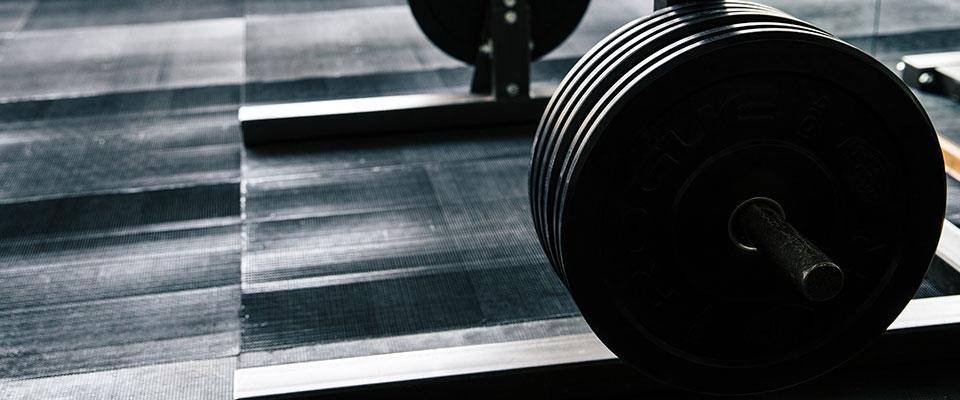 Barra para execução do exercício supino plano no treino de musculação | Holmes Place