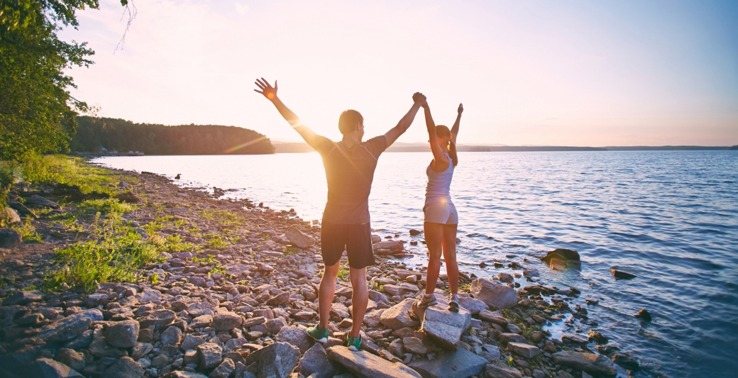 dwoje ludzi na plaży o zachodzie słońca | Holmes Place