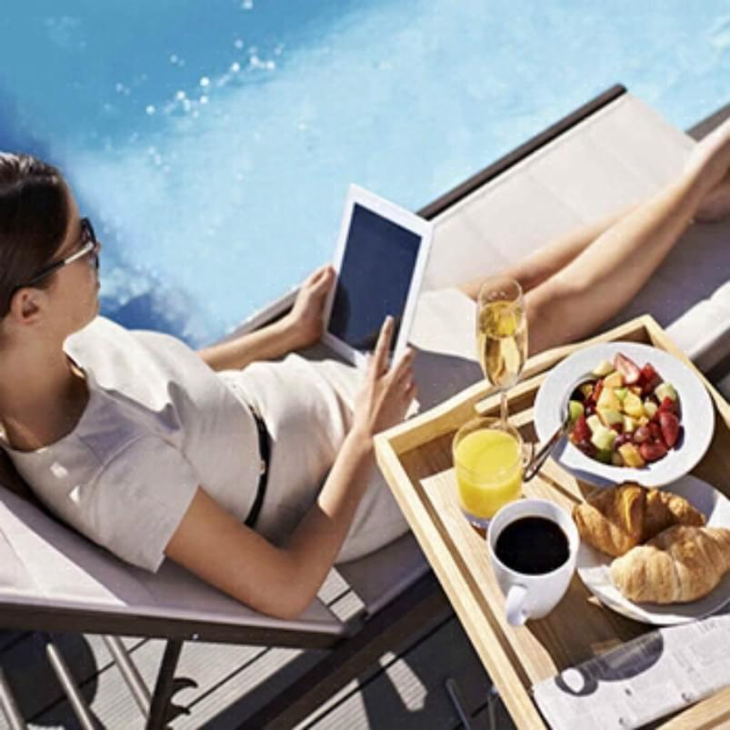 Holmes Place | woman eating breakfast by the swimming pool