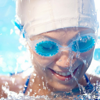 woman wearing head cap and swimming glasses close-up smile pool | Holmes Place