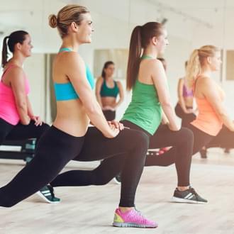 Grupo de mulheres a praticarem fitness para membros inferiores | Holmes Place
