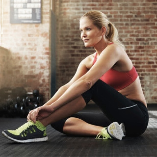 Holmes Place | woman fitness outfit in the gym sitting on the floor