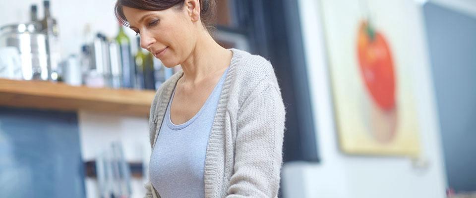 Mulher a cozinhar com erros que comprometem a dieta | Holmes Place