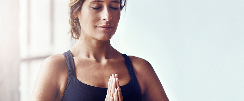 woman eyes closed meditation thankful fitness outfit Holmes Place