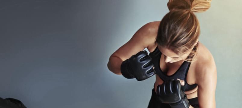 Frau lernt Techniken der Selbstverteidigung
