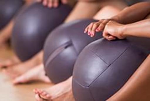 Mulher a segurar bola de pilates | Pilates Ball | Aula | Holmes Place