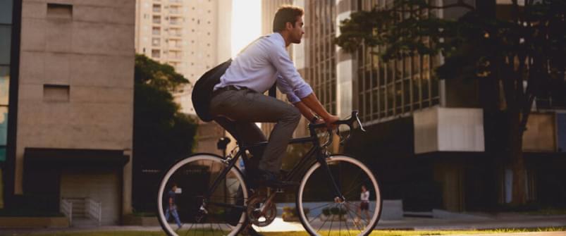 Mężczyzna jadący na rowerze w mieście | Holmes Place