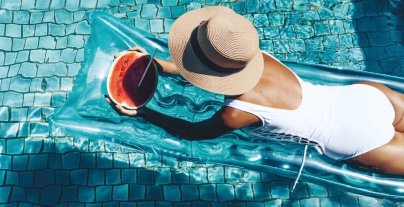 kobieta na materacu pływa w basenie Holmes Place