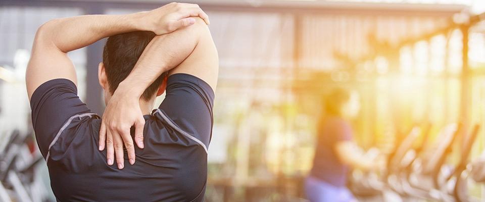 Homem a fazer exercícios de alongamento de ombros | Holmes Place